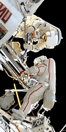 Experienced spacewalking cosmonaut shows new boy the ropes…as they both salute the original